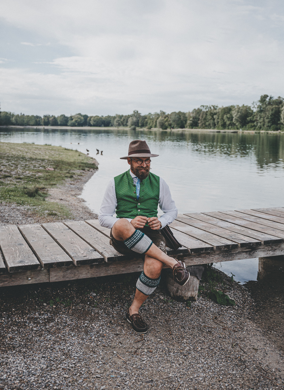 Albert wearing a hat and a green vest sitting next to a lake